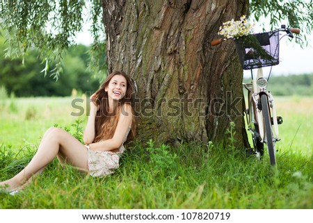 Woman relaxing under a tree next to a bicycle - stock photo