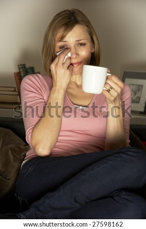 Woman Relaxing With Cup Of Coffee Watching Television - stock photo