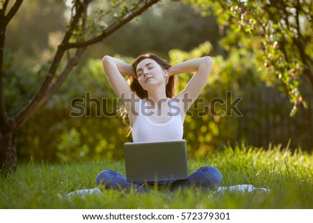 Woman relaxing with laptop at park