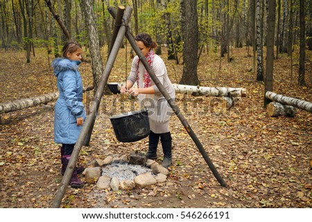 Woman removes hanging pot and daughter looks at she near bonfire in autumn forest