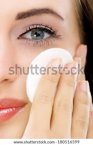 woman removing face makeup with cotton swab pad