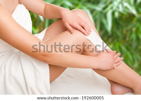 Woman removing hair from her legs with wax, in a green background