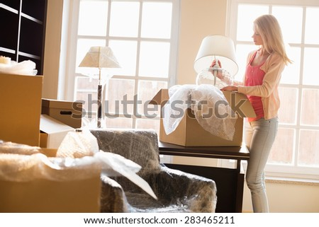 Woman removing lamp from moving box at new house