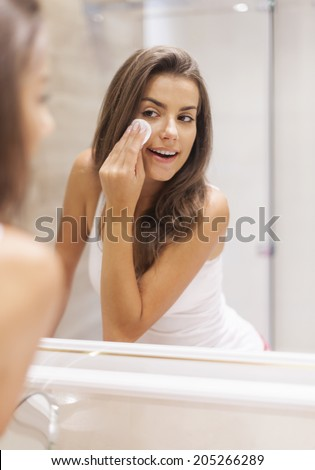Woman removing makeup from her face - stock photo