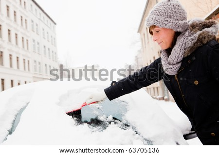 woman removing snow from car window - stock photo