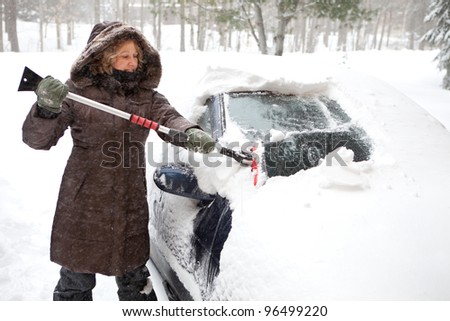 Woman removing snow from car windshield - stock photo