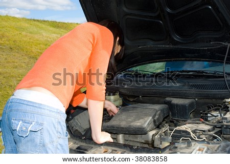Woman repairing a motor vehicle - stock photo