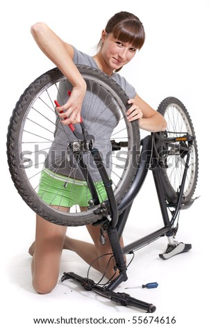 woman repairs bicycle with pliers - shot in studio on white background - stock photo