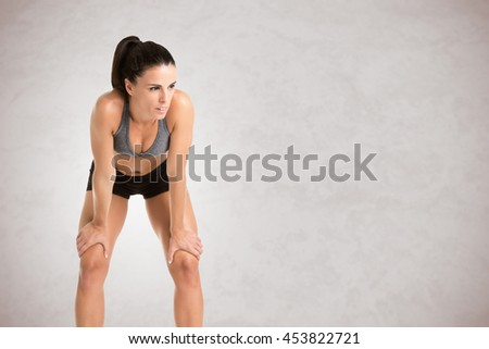 Woman resting after an workout, isolated in grey