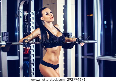 Woman resting after lifting barbell in gym - stock photo