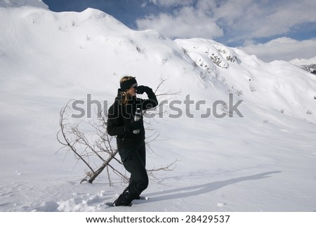 Woman resting and drinking hot tea in high alps in snow - stock photo