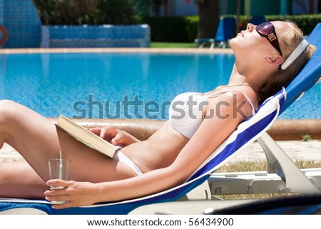 Woman resting at pool - stock photo
