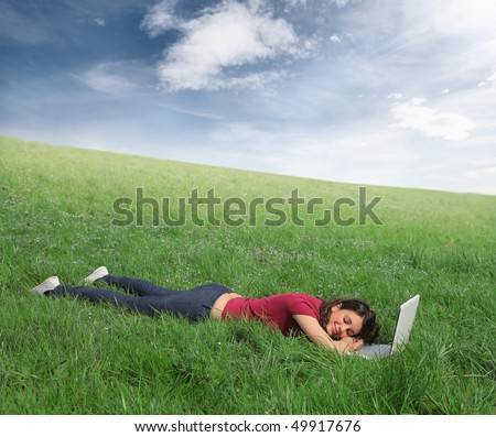 Woman resting on a green meadow with a laptop in front of her - stock photo