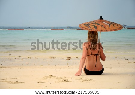 woman resting on the beach under sky - stock photo