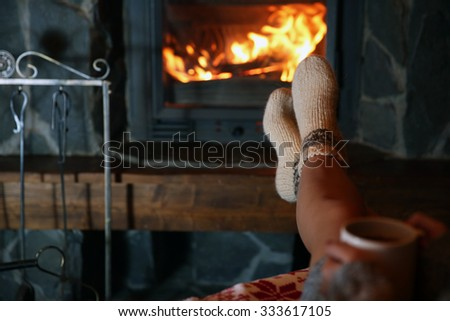 Woman resting with cup of hot drink near fireplace - stock photo