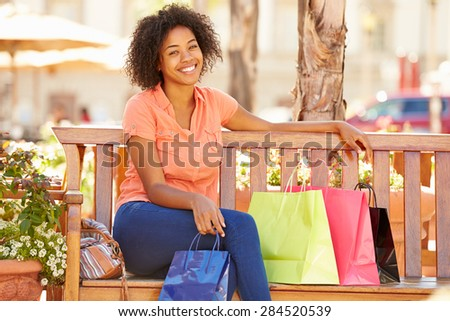 Woman Resting With Shopping Bags Sitting In Mall - stock photo