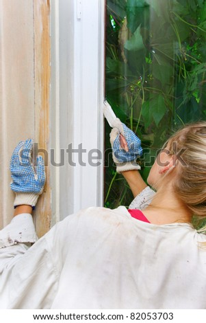 woman restores the window frame color - stock photo