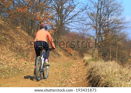 Woman rides a bike on a trail in sunny spring day