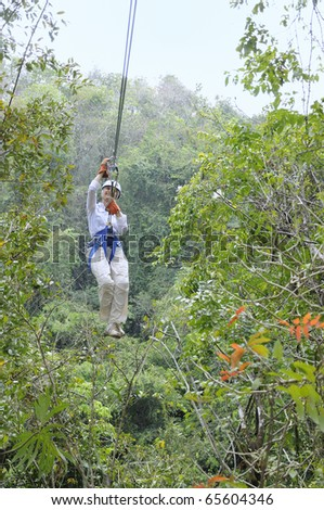 Woman rides a zip line above the rain-forest canopy - stock photo