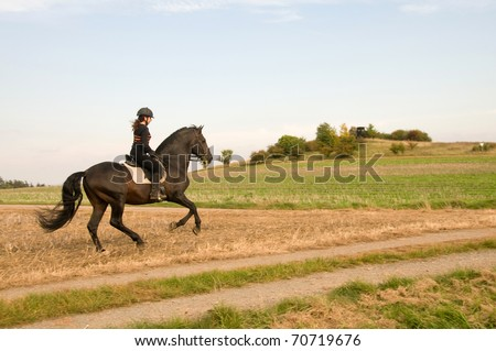 Woman rides at a gallop across the field.