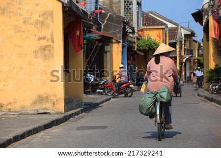 woman rides her bicycle in Hoi An, Vietnam. Hoi An - stock photo