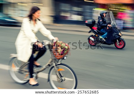 Woman riding a bicycle in the city, motorcyclist on background, motion blur. - stock photo