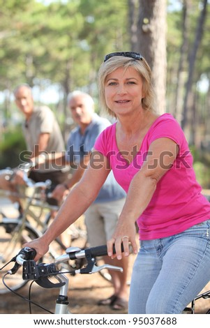 Woman riding a bike with friends in a forest - stock photo