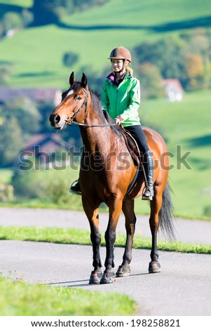 Woman riding a horse - stock photo