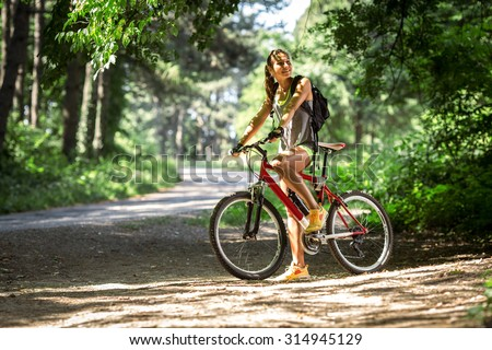Woman riding a mountain bike in the forest.Taking a break and looking around. - stock photo