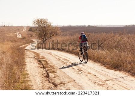 Woman riding a mountain bike on a rural  road, back view. - stock photo