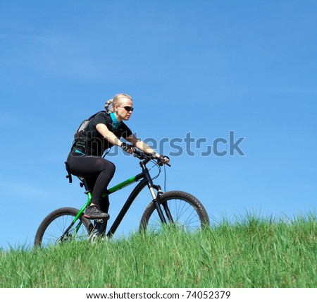 Woman riding a mountain bike over blue sky in spring nature