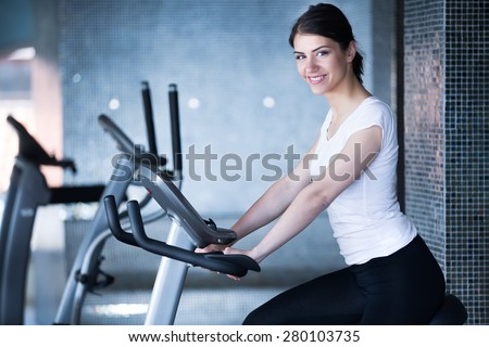 Woman riding an exercise bike in gym.Doing sport biking in the gym for fitness.Cardio and fat loss workout in the gym.Athletic woman pedaling on a stationary bike.Sport and fitness,summer body goals - stock photo
