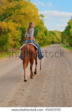 woman riding away on a horse and looking back, smiling. fall season. - stock photo