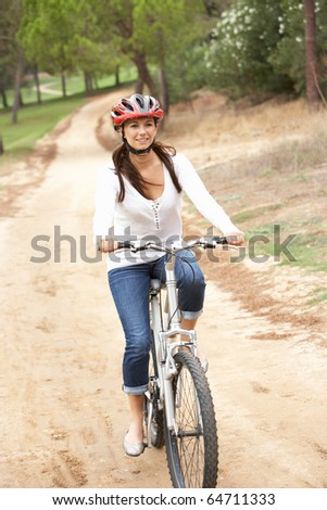 Woman riding bicycle in park - stock photo