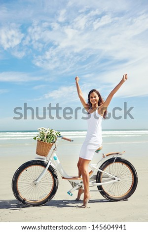 woman riding bicycle on beach in summer - stock photo
