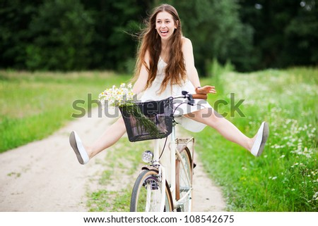 Woman riding bicycle with her legs in the air - stock photo