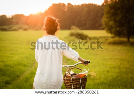 Woman riding bicycle with the basket of fresh. Color toned image. - stock photo