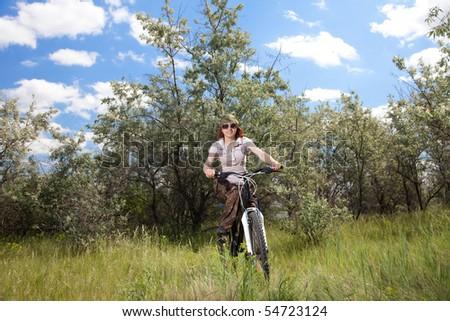 Woman riding bike in countryside - stock photo