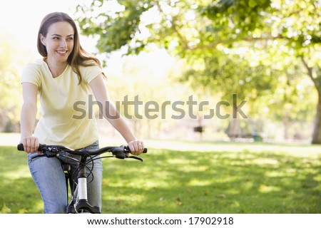 Woman riding bike in park - stock photo