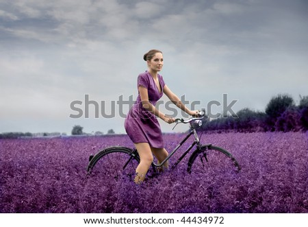 woman riding bike through a field of lilac flowers - stock photo