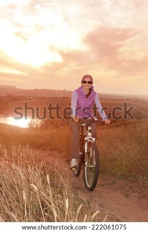 Woman riding cycle enjoying nature summer evening outdoors. Sunshine.  Soft red light. Soft focus. - stock photo