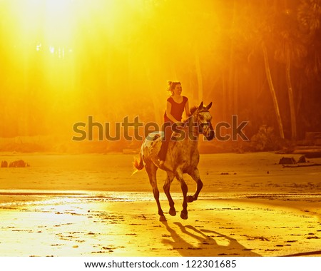 woman riding galloping horse on the beach at sunset - stock photo