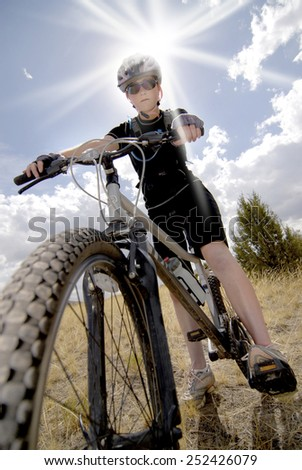 Woman Riding Mountain Bike with Sun and Sky in background - stock photo