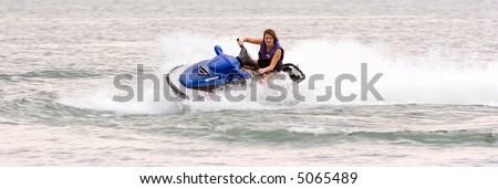Woman riding on seadoo jetski - stock photo