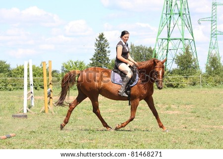 Woman riding on the chestnut horse - stock photo