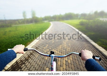 Woman riding pink bicycle in park, handlebar view. - stock photo