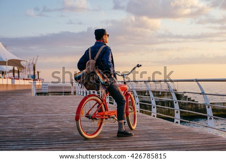 woman riding red vintage bicycle on seaside during sunset or sunrise - stock photo