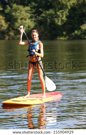 Woman riding stand-up-paddle on river