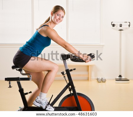 Woman riding stationary bicycle in health club - stock photo