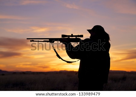 Woman Rifle Hunter Silhouetted at Sunset
